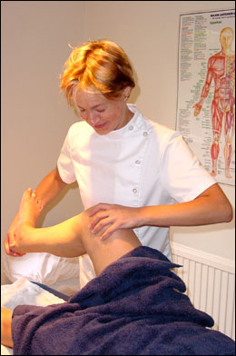 Emily Alexander examining the knee joint of a female patient at the Backworking Osteopathic Practice in Barnsbury, Islington, London N1